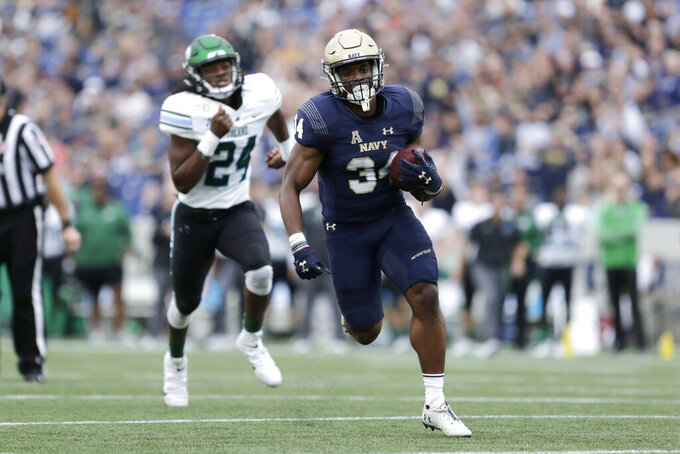 Navy fullback Jamale Carothers (34) runs with the ball while scoring a touchdown as Tulane linebacker Dorian Williams (24) chases him during the first half of an NCAA college football game, Saturday, Oct. 26, 2019, in Annapolis. (AP Photo/Julio Cortez)