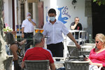 A bartender brings drinks to customers in a cafe of Saint Jean de Luz, southwestern France, Tuesday June 2, 2020. The French way of life resumes Tuesday with most virus-related restrictions easing as the country prepares for the summer holiday season amid the pandemic. Restaurants and cafes reopen Tuesday with a notable exception for the Paris region, the country's worst-affected by the virus, where many facilities will have to wait until June 22 to reopen. (AP Photo/Bob Edme)