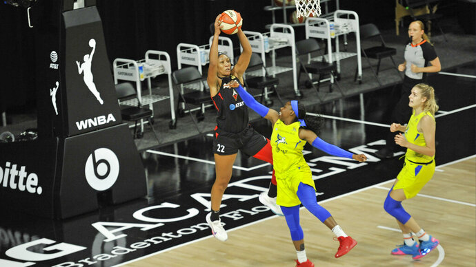 Las Vegas Aces' A'ja Wilson (22) grabs a rebound from Dallas Wings' Tyasha Harris, center, as Bella Alarie, right, watches during the first half of a WNBA basketball game Sunday, Aug. 2, 2020, in Bradenton, Fla. (AP Photo/Steve Nesius)