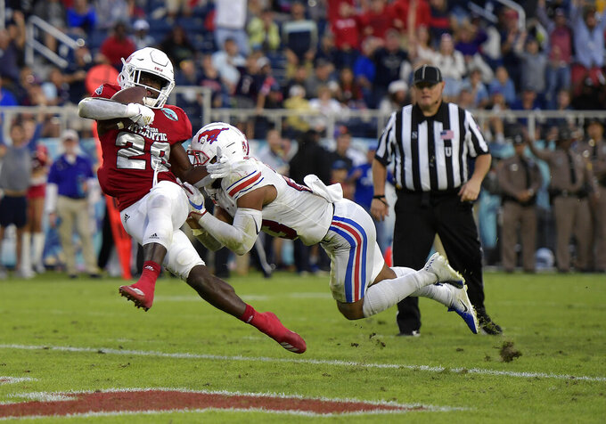 Florida Atlantic's James Charles, left, scores a touchdown against SMU's Tyeson Neals during the first half of  the Boca Raton Bowl NCAA college football game Saturday, Dec. 21, 2019, in Boca Raton, Fla. (Michael Laughlin/South Florida Sun-Sentinel via AP)