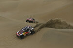 Driver Carlos Sainz and co-driver Lucas Cruz, both of Spain, race their Peugeot followed by teammates Cyril Despres, and co-driver David Castera, both of France, during the second stage of the 2018 Dakar Rally in Pisco, Peru, Sunday, Jan. 7, 2018. (AP Photo/Ricardo Mazalan)