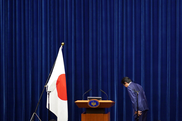 "FILE - In this March 14, 2020, file photo, Japanese Prime Minister Shinzo Abe bows to toward a Japanese flag before delivering his speech at the Prime Minister's office in Tokyo. Prime Minister Abe might be the biggest loser if the Tokyo Olympics don't go off as planned in just over four months. Abe has attached himself to the success of the Olympics since pushing hard for Tokyo's selection at an IOC meeting in 2013 in Buenos Aires, Argentina. Tokyo was picked over Istanbul by billing itself as a ""safe pair of hands."