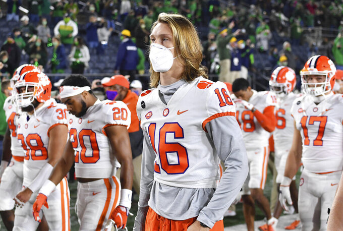 Clemson quarterback Trevor Lawrence (16) leaves the field with his teammates after Clemson lost to Notre Dame 47-40 in two overtimes during an NCAA college football game Saturday, Nov. 7, 2020, in South Bend, Ind. (Matt Cashore/Pool Photo via AP)