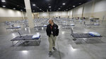 Salt Lake County Emergency Management Division Chief Clint Mecham walks between cots at the Mountain America Expo Center Monday, April 6, 2020, in Sandy, Utah. The State of Utah has contracted with Salt Lake County to use the Mountain America Expo Center as an alternate care site, or hospital overflow. This is not a site for COVID-19 patients. It is simply an overflow site for certain types of care, should the need arise. It will initially be stocked with 250 beds and medical equipment. (AP Photo/Rick Bowmer)