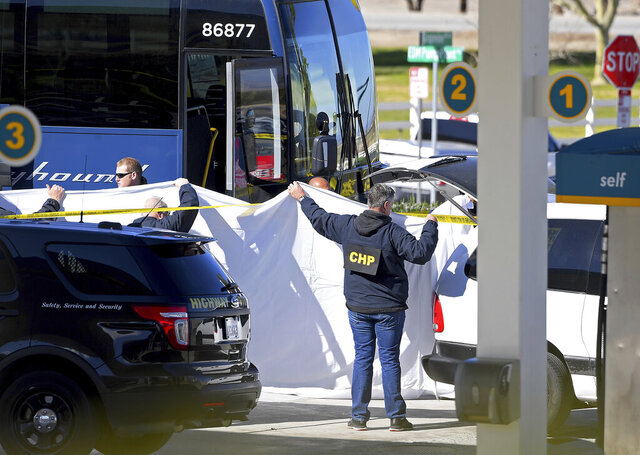 Coroner's officials work behind a drape to remove the body of a person who was killed when a gunman opened fire aboard a packed Greyhound bus, and wounded five others before the driver pulled over onto the shoulder and the killer got off, in Lebec, Calif., some 75 miles north of Los Angeles, Monday, Feb. 3, 2020.. The suspect was taken into custody without incident, and authorities say the the motive is unknown. The bus was traveling from Los Angeles to San Francisco on Interstate 5 at the time of the shooting early Monday. (AP Photo/Jayne Kamin-Oncea)
