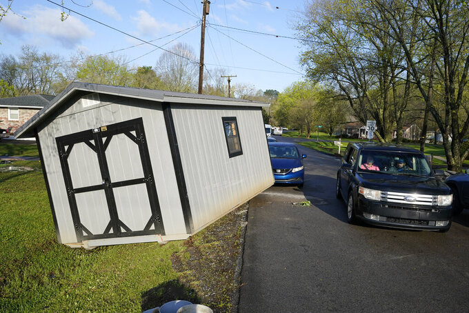 A vehicle passes a utility building that was carried onto a street by floodwaters Sunday, March 28, 2021, in Nashville, Tenn. Heavy rain across Tennessee flooded homes and roads as a line of severe storms crossed the state. (AP Photo/Mark Humphrey)