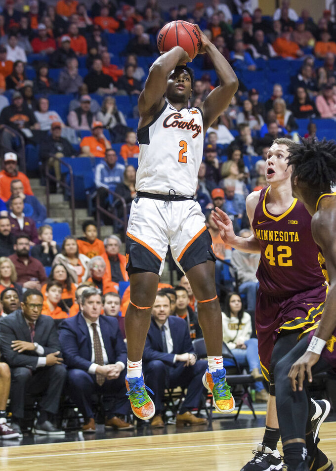 Oklahoma State guard Chris Harris Jr. shoots past Minnesota forward Michael Hurt during an NCAA college basketball game Saturday, Dec. 21, 2019, in Tulsa, Okla. (Brett Rojo/Tulsa World via AP)