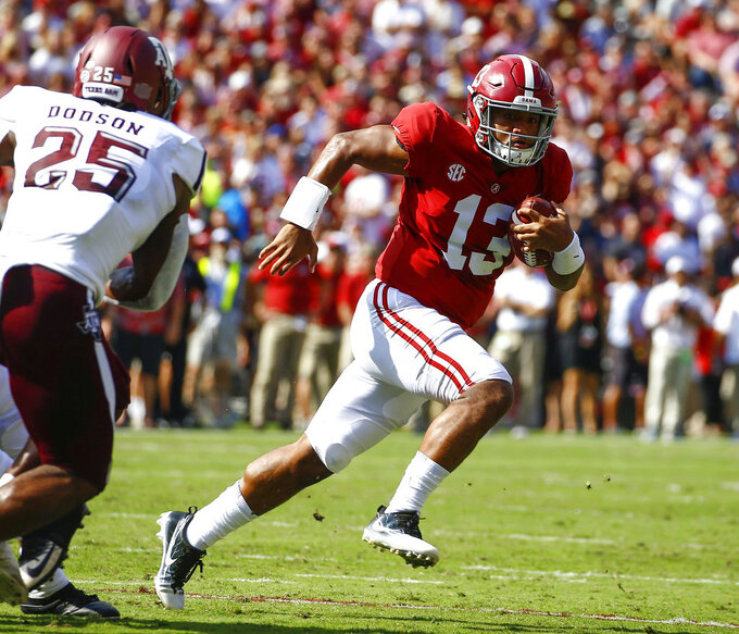 FILE - In this Sept. 22, 2018, file photo, Alabama quarterback Tua Tagovailoa (13) scrambles for a first down against Texas A&M during the first half of an NCAA college football game, in Tuscaloosa, Ala. Tagovailoa was named to The Associated Press Midseason All-America NCAA college football team, Tuesday, Oct. 16, 2018. (AP Photo/Butch Dill, File)