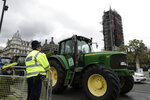 Farmers from the group Save British Farming drive tractors around Parliament Square, backdropped by the Houses of Parliament and the scaffolded Big Ben tower in London, in a protest against cheaply produced lower standard food being imported from the U.S. after Brexit that will undercut them, Wednesday, July 8, 2020. (AP Photo/Matt Dunham)
