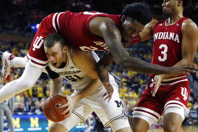 Indiana forward De'Ron Davis (20) falls over Michigan forward Austin Davis (51) during the second half of an NCAA college basketball game, Sunday, Feb. 16, 2020, in Ann Arbor, Mich. (AP Photo/Carlos Osorio)