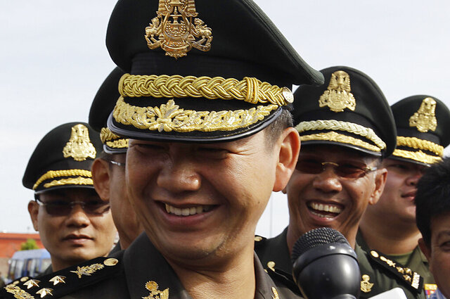 In this Jan. 5, 2017, photo, Lt. Gen. Hun Manet, foreground, smiles as his attends a Buddhist ceremony in Phnom Penh, Cambodia. Cambodia's long-serving Prime Minister Hun Sen on June 8, 2020, appointed his eldest son, Hun Manet, 42 years old, to head his ruling party's youth wing, an appointment further fueling speculation he is being groomed to succeed his father as the Southeast Asian country's leader. (AP Photo/Heng Sinith)