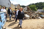 German Chancellor Angela Merkel, center, informs herself in the district of Iversheim about the situation in the flood-affected area and meet victims of the flood disaster Tuesday, July 20, 2021. (Wolfgang Rattay/Pool Photo via AP)