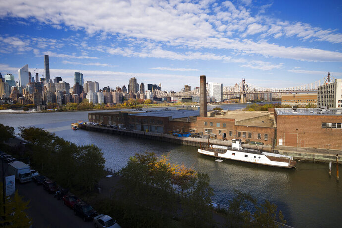 FILE- In this Nov. 7, 2018, file photo, a rusting ferryboat is docked next to an aging industrial warehouse on Long Island City's Anable Basin in the Queens borough of New York. Amazon said Thursday, Feb. 14, 2019, that it will not be building a new headquarters in New York, a stunning reversal after a yearlong search. (AP Photo/Mark Lennihan, File)