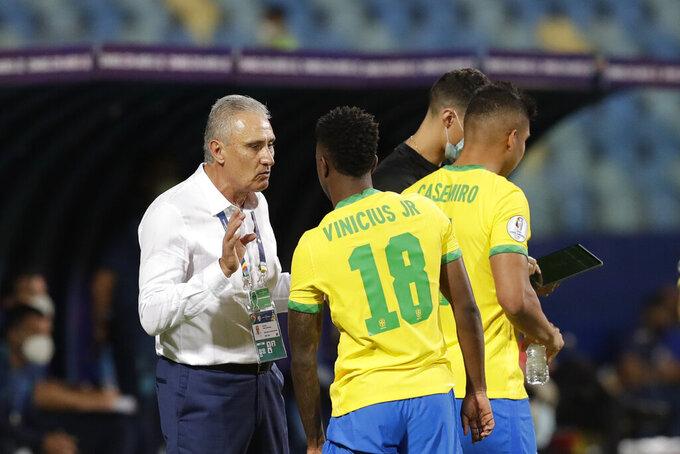 Brazil's coach Tite, left, gives instructions to his player Vinicius Junior during a Copa America soccer match against Ecuador at Olimpico stadium in Goiania, Brazil, Sunday, June 27, 2021. (AP Photo/Eraldo Peres)