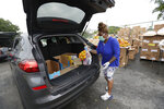 Viv Brown with the Women Supporting Women's support group, loads a car during a food distribution event, Wednesday, April 1, 2020, in the Liberty City neighborhood of Miami. The event was supported by the city, Ark of the City and Farm Share. (AP Photo/Wilfredo Lee)