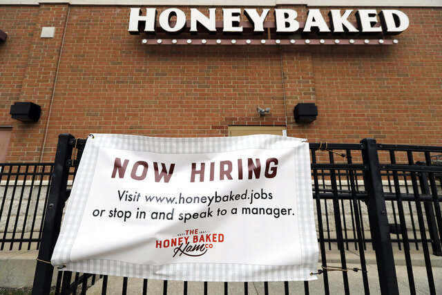 A sign advertising hiring is posted outside the HoneyBaked store in Rolling Meadows, Ill., Friday, April 3, 2020. Employers are still hiring during coronavirus pandemic. (AP Photo/Nam Y. Huh)
