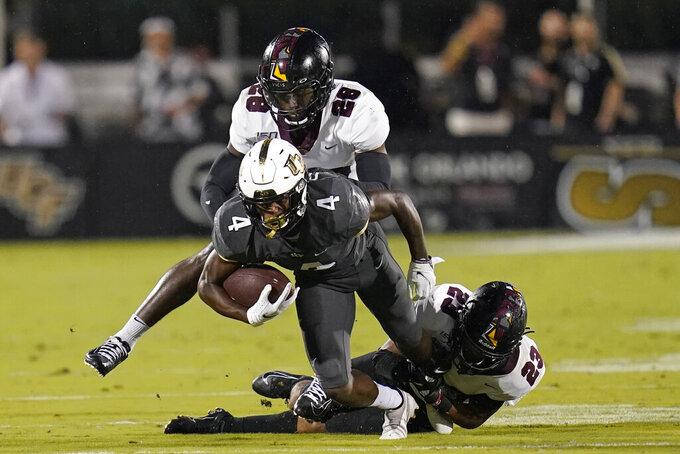 Central Florida wide receiver Ryan O'Keefe (4) is, stopped after a reception, by Bethune-Cookman cornerback Henry Miller II (28) and safety Uriah Ratliff (23) during the first half of an NCAA college football game Saturday, Sept. 11, 2021, in Orlando, Fla. (AP Photo/John Raoux)