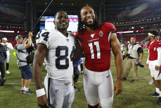 Arizona Cardinals wide receiver Larry Fitzgerald (11) and Oakland Raiders wide receiver Antonio Brown (84) meet at midfield after an an NFL preseason football game, Thursday, Aug. 15, 2019, in Glendale, Ariz. The Raiders won 33-26. (AP Photo/Ralph Freso)