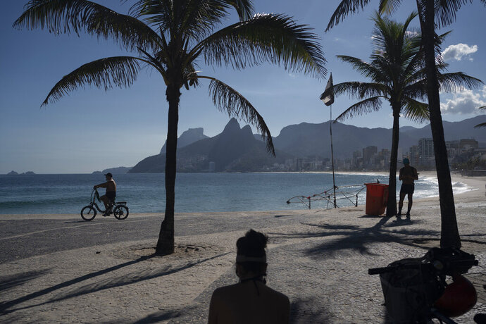 A man rides his bicycle along an empty Arpoador beach in Rio de Janeiro, Brazil, Thursday, March 26, 2020, as many people stay home to help contain the spread of the new coronavirus. (AP Photo/Leo Correa)