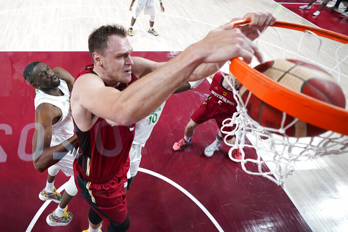 Germany's Johannes Voigtmann dunks the ball ahead of Nigeria's Ekpe Udoh, left, during a men's basketball preliminary round game at the 2020 Summer Olympics, Wednesday, July 28, 2021, in Saitama, Japan. (Charlie Neibergall/Pool Photo via AP)
