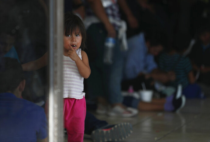 A migrant child looks at the camera while her parents wait at an immigration center on the International Bridge 1, in Nuevo Laredo, Mexico, Tuesday, July 16, 2019. A U.S. policy to make asylum seekers wait in Mexico while their cases wind through clogged U.S. immigration courts has also expanded to the violent city of Nuevo Laredo. (AP Photo/Marco Ugarte)