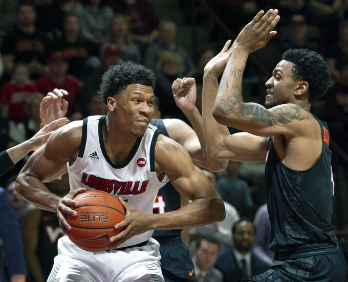 Louisville forward Dwayne Sutton, left, looks to pass against Virginia Tech Hokies guard Nickeil Alexander-Walker (4) during the first half of an NCAA college basketball game Monday, Feb. 4, 2019, in Blacksburg, Va. Louisville won 72-64. (AP Photo/Don Petersen)