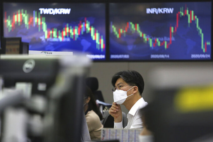 A currency trader adjusts his face mask at the foreign exchange dealing room of the KEB Hana Bank headquarters in Seoul, South Korea, Thursday, Sept. 24, 2020. Asian shares were mostly lower Thursday as caution again after a retreat on Wall Street driven by a decline in technology shares.(AP Photo/Ahn Young-joon)