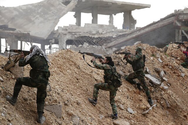 FILE - In this Dec. 5, 2016 file photo, Syrian army soldiers fire their weapons during a battle with rebel fighters at the Ramouseh front line, east of Aleppo, Syria. In a world gripped by a pandemic, global unrest and a fast-moving news cycle, it can be difficult to remember that the war in Syria is still happening. (AP Photo/Hassan Ammar, File)