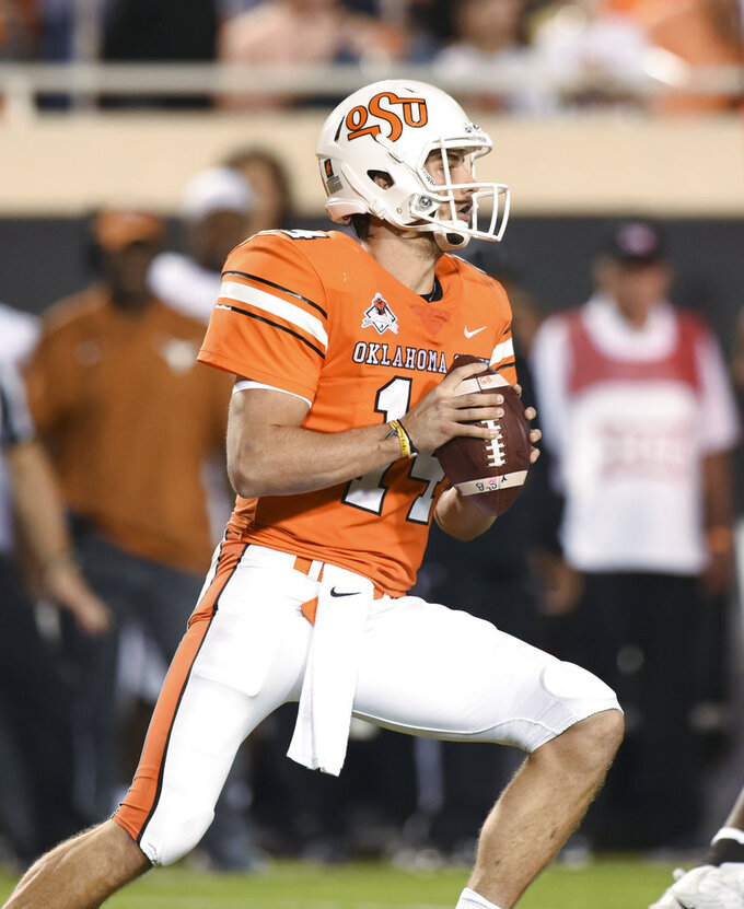 Oklahoma State quarterback Taylor Cornelius looks for an open teammate in the second half of an NCAA college football game in Stillwater, Okla., Saturday, Oct. 27, 2018. Cornelius threw for 321 yards in the Oklahoma State 38-35 win over Texas. (AP Photo/Brody Schmidt)