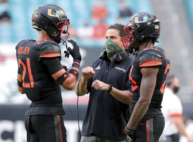 FILE - In this Dec. 12, 2020, file photo, Miami coach Manny Diaz talks with safety Bubba Bolden (21) during the first half of the team's NCAA college football game against North Carolina in Miami Gardens, Fla, A lopsided loss to end the regular season cost coach Diaz's team a spot in a major bowl. Instead, the Hurricanes (8-2) will finish their best season in years on a smaller stage on Tuesday night, against Oklahoma State in the Cheez-It Bowl. (Al Diaz/Miami Herald via AP, File)