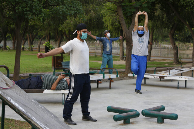 People exercise in a park in Lahore, Pakistan, Friday, June 5, 2020. Government of Pakistan's Punjab province has reopened parks in different cities of the province including Lahore amid coronavirus outbreak. (AP Photo/K.M. Chaudary)