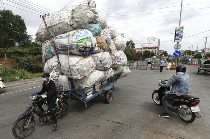 A man transporting huge bags of recyclables is turned back at a blocked street in a zone where the COVID-19 cases are rising sharply in Stung Meanchey complex outside Phnom Penh, Cambodia, Friday, May 7, 2021. Cambodia on Thursday eased a major restriction it had imposed to battle a major coronavirus outbreak, allowing travel in and out of the capital Phnom Penh and the satellite town of Takhmao. The travel ban has been in effect for three weeks so far. (AP Photo/Heng Sinith)