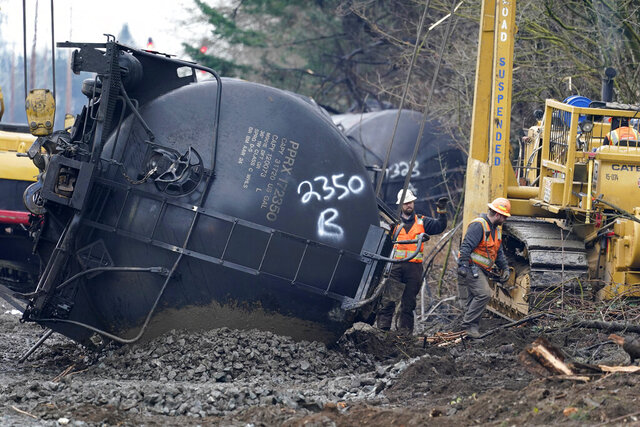 Workers use heavy equipment to begin to move one of several train cars which had been hauling crude oil and derailed a week earlier, Tuesday, Dec. 29, 2020, in Custer, Wash. The cause of the derailment of the oil cars Dec. 22 in Whatcom County is still unknown. A spokesperson for BNSF Railways said three cars ruptured, spilling an unknown amount of crude oil onto the ground. (AP Photo/Elaine Thompson)