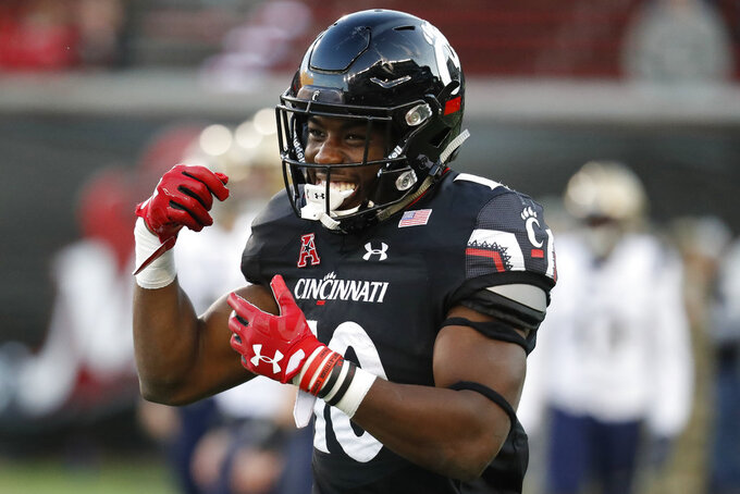 Cincinnati running back Charles McClelland celebrates after scoring a touchdown in the second half of an NCAA college football game against Navy, Saturday, Nov. 3, 2018, in Cincinnati. (AP Photo/John Minchillo)