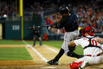 Miami Marlins' Curtis Granderson, left, follows through after hitting a two-run double off Philadelphia Phillies relief pitcher Jose Alvarez during the sixth inning of a baseball game, Saturday, April 27, 2019, in Philadelphia. Phillies catcher J.T. Realmuto, right, looks on. (AP Photo/Matt Slocum)