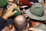 A Lebanese retired special forces soldier shouts slogans, as he tries with other protesters to enter the parliament building where lawmakers and ministers are discussing the draft 2019 state budget, in Beirut, Lebanon, Friday, July 19, 2019.  The budget is aimed at averting a financial crisis in heavily indebted Lebanon. But it was met with criticism for failing to address structural problems. Instead, the budget mostly cuts public spending and raises taxes.  (AP Photo/Hussein Malla)