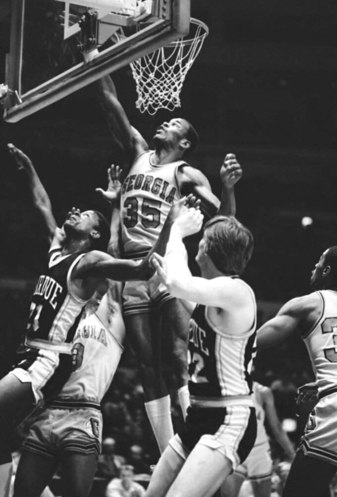 In this March 22, 1982, file photo, Georgia's Terry Fair (35) goes up with the ball with Purdue's Ricky Hall, left, and teammate Dan Palombizio, right, in close range during the first half of a semifinal game in the National Invitation Tournament at New York's Madison Square Garden. Fair, a key player on Georgia only men's Final Four team, has died at the age of 59, the school announced, Friday, Jan. 31, 2020. The university said Fair died Thursday of natural causes in his hometown of Macon, Ga. (AP Photo/Richard Drew, File)