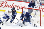 Toronto Maple Leafs' Auston Matthews (34) cannot get a shot past Winnipeg Jets goaltender Laurent Brossoit (30) as Jets' Josh Morrissey (44) also defends during third-period NHL hockey game action in Winnipeg, Manitoba, Thursday, Jan. 2, 2020. (John Woods/The Canadian Press via AP)