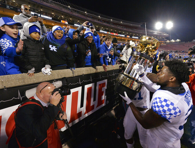 Kentucky linebacker Jamar Watson holds up the Governor's Cup to the fans following Kentucky's 56-10 victory over Louisville in an NCAA college football game, in Louisville, Ky., Saturday, Nov. 24, 2018. (AP Photo/Timothy D. Easley)