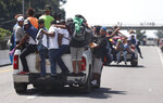 Central American migrants making their way to the U.S. in a large caravan cling to the trucks of drivers who offered them free rides, as they arrive to Tapachula, Mexico, Sunday, Oct. 21, 2018. Despite Mexican efforts to stop them at the Guatemala-Mexico border, about 5,000 Central American migrants resumed their advance toward the U.S. border Sunday in southern Mexico. (AP Photo/Moises Castillo)