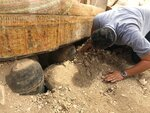 """This photo provided by the Egyptian Ministry of Antiquities shows Egyptian Minister of Antiquities Khaled el-Anany looking at recently discovered ancient colored coffins with inscriptions and paintings, in the southern city of Luxor, Egypt, Tuesday, Oct. 15, 2019. The ministry said archeologists found at least 20 wooden coffins in the Asasif Necropolis, describing it as one of the """"biggest and most important"""" discoveries in recent years. (Egyptian Ministry of Antiquities via AP)"""