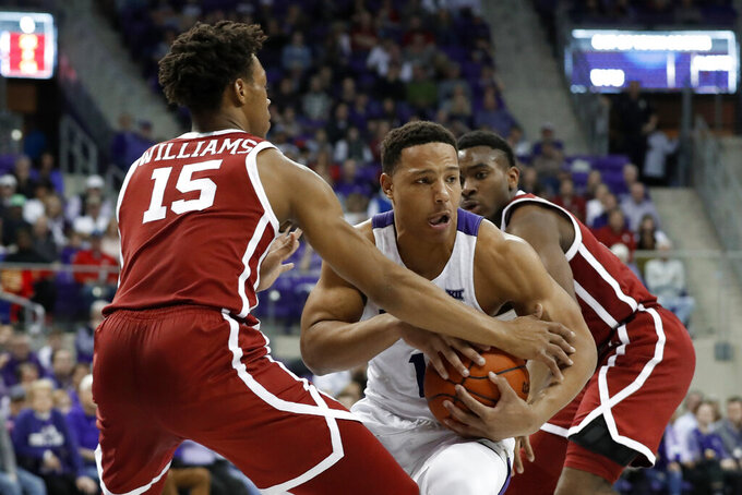 Oklahoma guard Alondes Williams (15) defends as TCU guard Desmond Bane (1) works beneath the basket for a shot attempt in the second half of an NCAA college basketball game in Fort Worth, Texas, Saturday, March 7, 2020. (AP Photo/Tony Gutierrez)