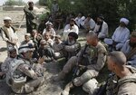 FILE - This July 2, 2009, photo shows Josh Habib, far left, a 53-year-old translator for the U.S. Marines, speaking with Afghan villagers and two Marines in the Nawa district of Afghanistan's Helmand province. More than 200 Afghans were due to land Friday, July 30, 2021 in the United States in the first of several planned evacuation flights for former translators and others as the U.S. ends its nearly 20-year war in Afghanistan. (AP Photo/David Guttenfelder)