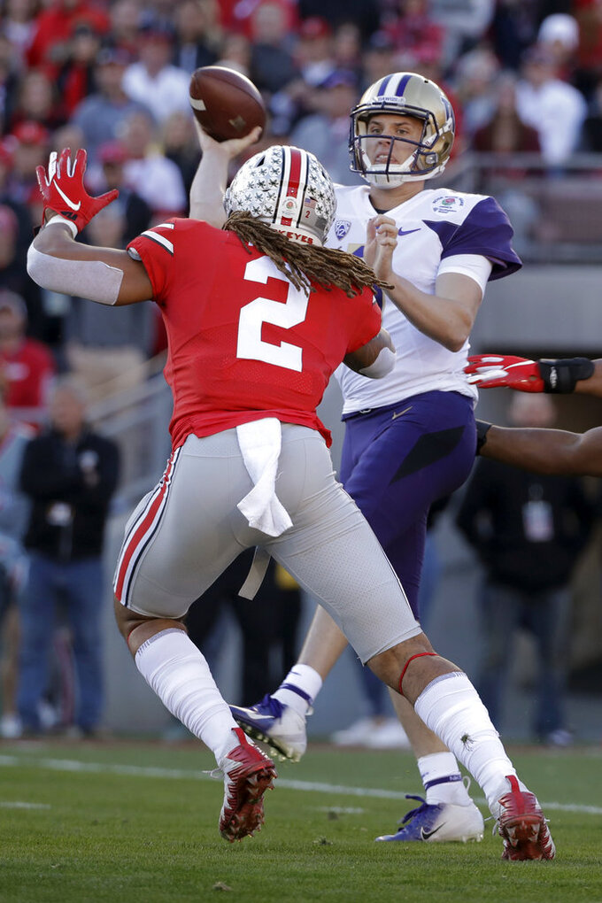 Washington quarterback Jake Browning throws a pass under pressure from Ohio State defensive end Chase Young during the first half of the Rose Bowl NCAA college football game Tuesday, Jan. 1, 2019, in Pasadena, Calif.(AP Photo/Jae C. Hong)