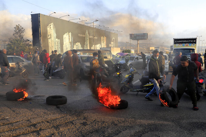 Protesters set burning tires on fire to block a highway that leads to Beirut's international airport, during a protest against against the economic and financial crisis, in Beirut, Lebanon, Tuesday, March 2, 2021. The Lebanese pound has hit a record low against the dollar on the black market as the country's political crisis deepens and foreign currency reserves dwindle further. (AP Photo/Hussein Malla)