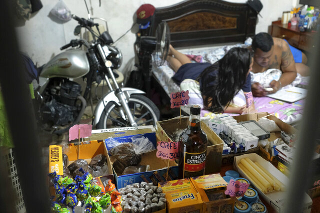 Food items, cigarettes and candles sit for sale behind the burglar bars of a private residence, where a couple calculates their sales from their bed in the Santa Rosalia neighborhood of Caracas, Venezuela, Sunday, Aug. 23, 2020. Strict measures aimed at slowing the spread of COVID-19 have left many without work, so some Venezuelans have turned their homes and other spaces into makeshift take-out restaurants or shops as they struggle to get by during the coronavirus lockdown.  (AP Photo/Matias Delacroix)