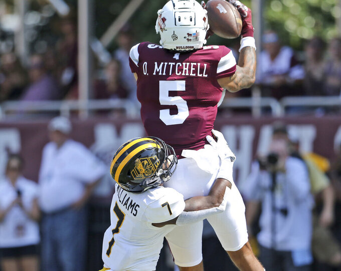 Mississippi State wide receiver Osirus Mitchell (5) catches a pass for a touchdown as Southern Mississippi defensive back Ty Williams (7) tackles him in the first half of an NCAA college football game Saturday, Sept. 7, 2019, in Starkville, Miss. (AP Photo/Jim Lytle)