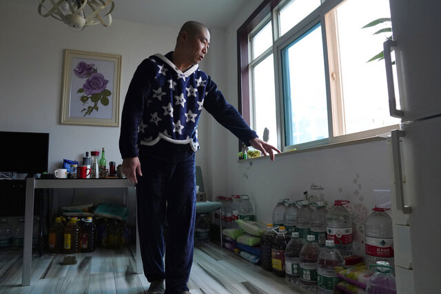 Wuhan resident Zhu Tao talks about his stockpile of supplies at home in Wuhan in central China's Hubei province on Wednesday, Oct. 21, 2020. Zhu, a government critic, took precautions against the virus early and felt vindicated when the outbreak exploded and the city went into lockdown. But now that the situation is back to something close to normal in Wuhan, Zhu finds himself at odds with his neighbors and the government. (AP Photo/Ng Han Guan)