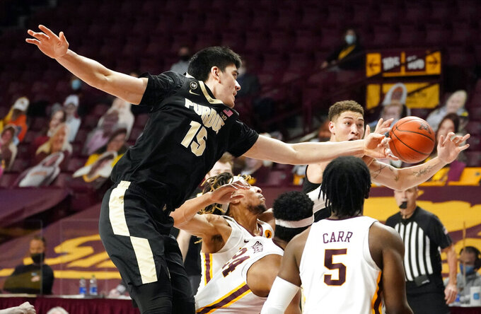 Purdue's Zach Edey (15) makes a pass to Mason Gillis, top right, amidst Minnesota defenders in the second half of an NCAA college basketball game, Thursday, Feb. 11, 2021, in Minneapolis. (AP Photo/Jim Mone)