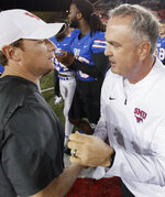 Houston coach Major Applewhite, left, and SMU coach Sonny Dykes shake hands after an NCAA college football game Saturday, Nov. 3, 2018, in Dallas. SMU won 45-31. (AP Photo/Brandon Wade)